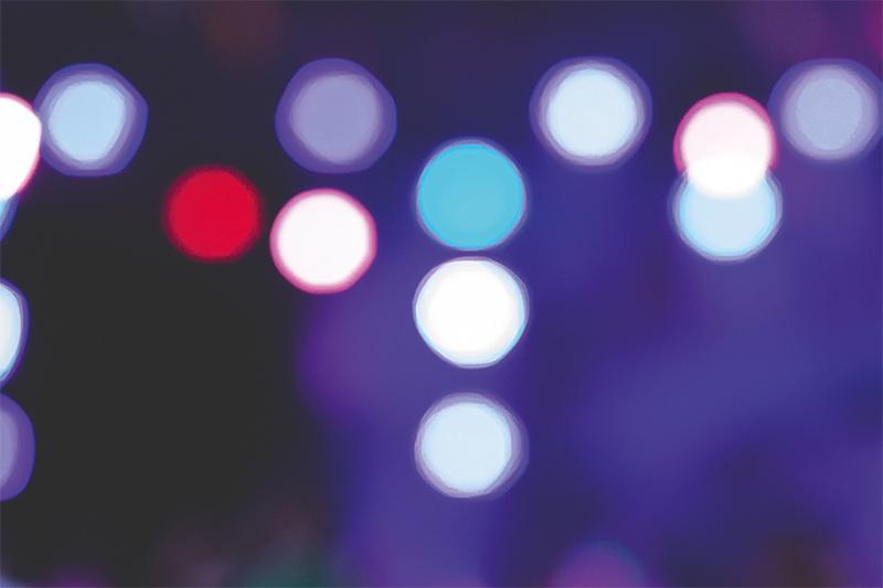 Das Bild zeigt unscharfe Stadtlichter in der Nacht.